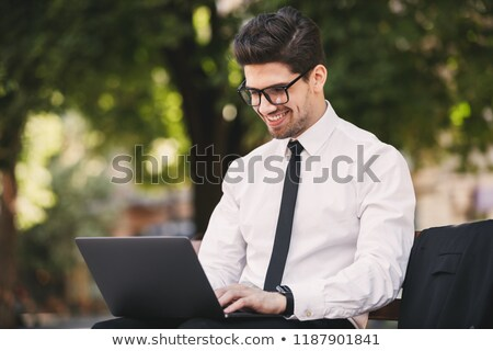 Photo of smiling man in businesslike suit sitting on bench in gr Stock photo © deandrobot