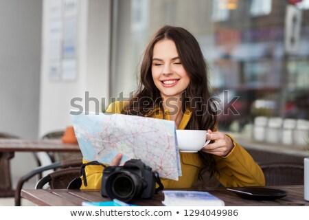 happy woman with map drinking cocoa at city cafe Stock photo © dolgachov