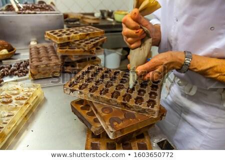 confectioner makes chocolate dessert at sweet-shop Stock photo © dolgachov