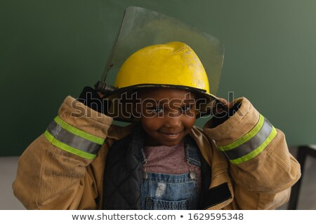 Front view of a black  schoolgirl with a too big fire uniform looking at camera in classroom of elem Stock photo © wavebreak_media