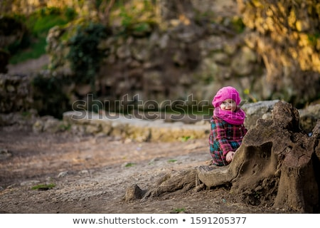 A little girl walks in a nature Park and came across a stone wall overgrown with natural flowers Stock photo © ElenaBatkova