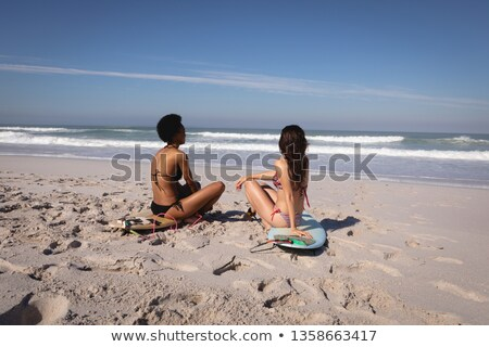 Rear view of young multi ethnic women sitting on surfboards in front of the sea at beach in the suns Stock photo © wavebreak_media
