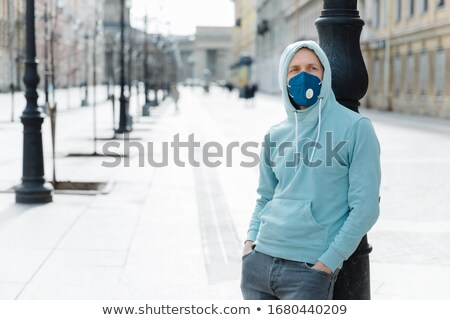 Serious pensive man wears hoodie and protective respiratory mask while walk on street, protects agai Stock photo © vkstudio