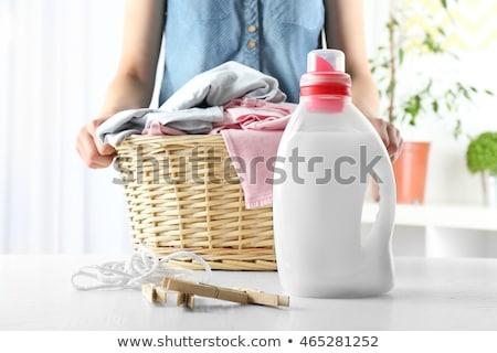 woman with basket and laundry detergent at home Stock photo © dolgachov