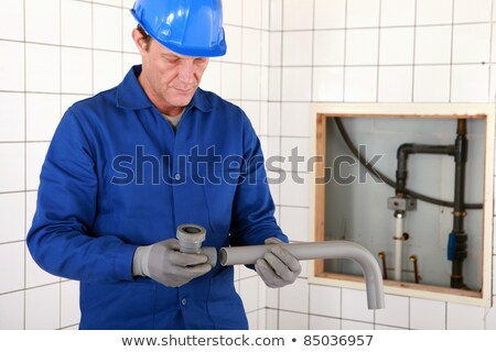 Stock photo: Artisan fitting two parts of pipe together