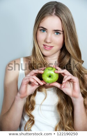 cheerful woman holding apples on head stock photo © deandrobot