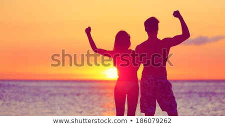 Silhouette of athletic young man showing biceps at sunnrise Stock photo © deandrobot