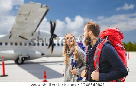smiling man with backpack over plane on airfield Stock photo © dolgachov
