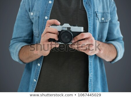 Millennial man mid section with camera against grey background with grunge overlay Stock photo © wavebreak_media