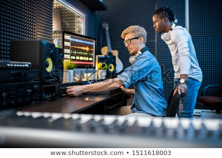 Young casual man adding volume while recording music with his African colleague Stock photo © pressmaster