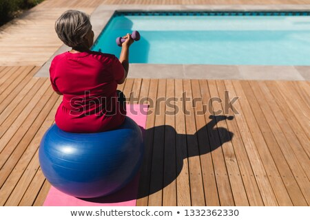 Rear view of senior African American woman exercising with dumbbells on a swiss ball in front of the Stock photo © wavebreak_media