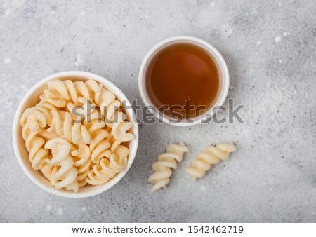 Salt and vinegar potato twirls in white bowl, classic snack on light kitchen table background.  Stock photo © DenisMArt