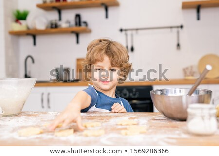 Cute little boy in apron stretching hand to one of raw cookies on table Stock photo © pressmaster