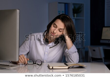 Tired female operator with closed eyes napping by desk while working late Stock photo © pressmaster