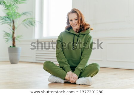 Happy ginger female sport trainer sits crossed legs on floor, wears green hoody and trousers, white  Stock photo © vkstudio