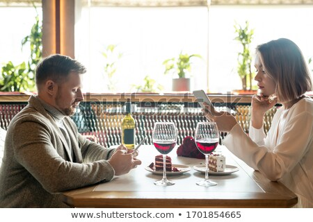 People sitting on restaurant table toasting with red wine Stock photo © Kzenon