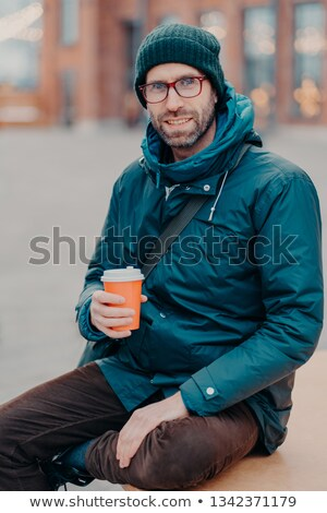 Stylish Caucasian man has free time, poses outside with disposable cup of coffee, dressed in hat and Stock photo © vkstudio