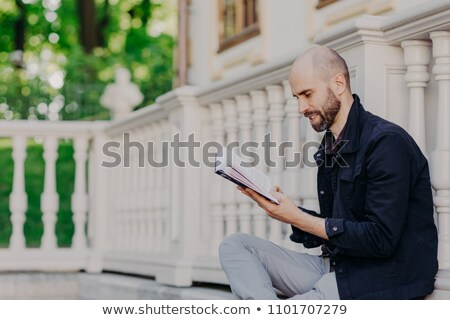 Sideways shot of bearded male with bald, holds book, sits outdoor against white balcony background,  Stock photo © vkstudio