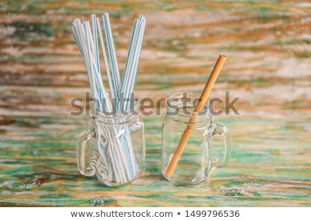 Bamboo drinking straw vs disposable straws on wooden painted background. Zero waste concept Stock photo © galitskaya