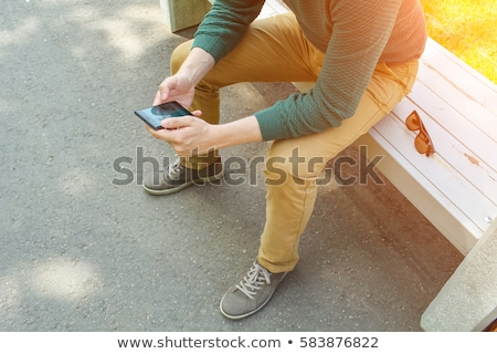 Portrait of a handsome young man sitting in the sun on bench at  Stock photo © HASLOO