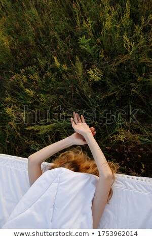 Beautiful female laying on the flower field Stock photo © Anna_Om