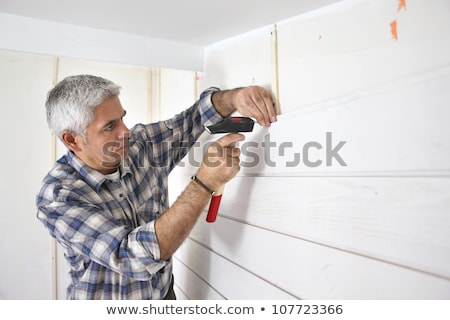grey haired man replacing house paneling stock photo © photography33