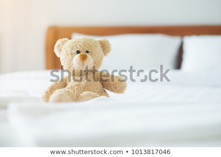 Stock photo: Girl lying on bed with teddy bear