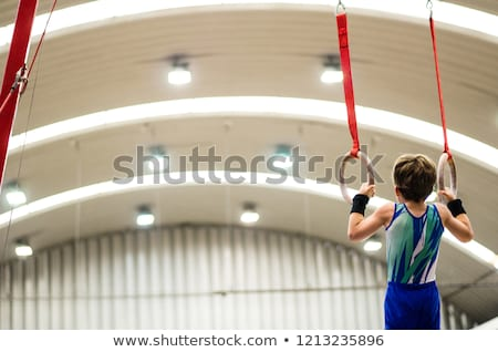 Young gymnast training on rings  Stock photo © dacasdo