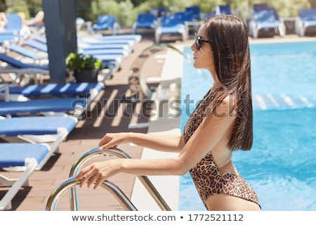 Side view portrait of a woman in bikini coming out from swimming pool Stock photo © deandrobot
