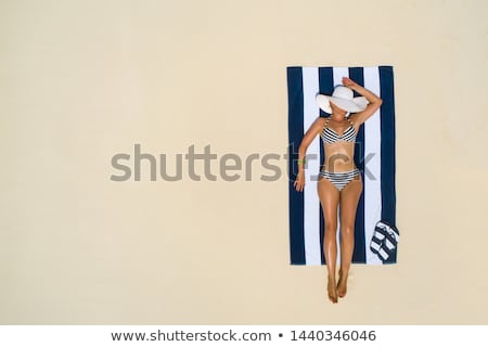 young woman sunbathing on beach stock photo © dolgachov