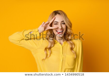 Cheerful girl winking and showing peace sign Stock photo © deandrobot