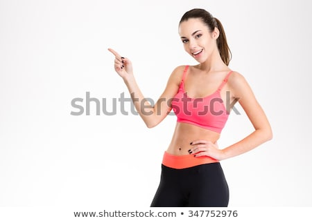 cheerful attractive young fitness woman pointing away stock photo © deandrobot