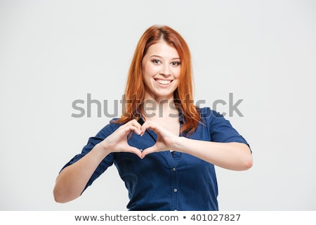 cheerful beautiful redhead young woman making heart by hands stock photo © deandrobot