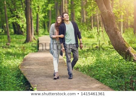 Portrait of a beautiful couple walking in park Stock photo © deandrobot