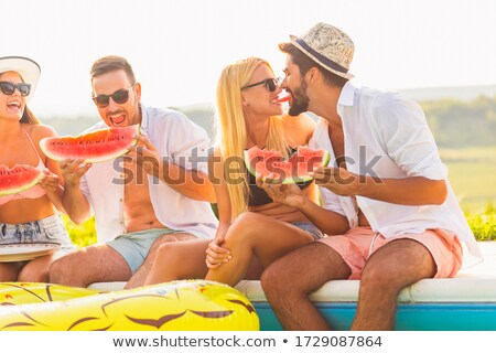 Happy beautiful girls in bikini eating watermelon at the pool stock photo © deandrobot