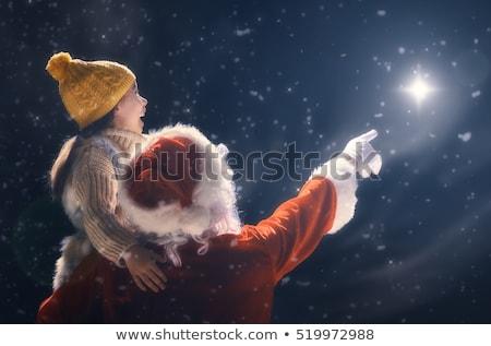 girl and santa claus looking at christmas star stock photo © choreograph