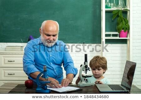 Portrait of happy boy with grandfather sitting by wall Stock photo © wavebreak_media