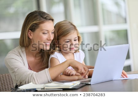girl on mothers lap looking at computer Stock photo © IS2