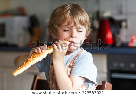boy eating bread roll stock photo © is2