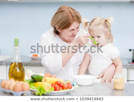 nagymama · etetés · baba · jókedv · vacsora · eszik - stock fotó © IS2