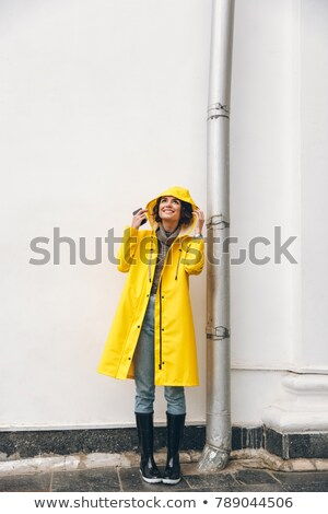 Satisfied adult girl 20s wearing yellow coat standing with hood  Stock photo © deandrobot