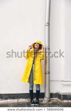 Photo stock: Satisfied Adult Girl 20s Wearing Yellow Coat Standing With Hood