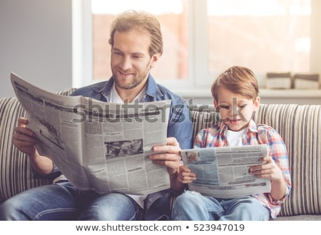 portrait of a smiling young man reading newspaper stock photo © deandrobot