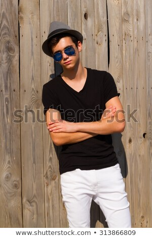 portrait of young man wearing sunglasses leaning against lightin stock photo © feedough