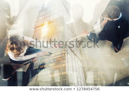 Rival business man and woman compete for the command by pulling the rope. Double exposure effect Stock photo © alphaspirit