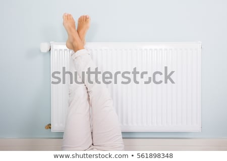 Stock photo: Woman Warming Up Her Feet On Radiator