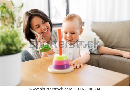 baby boy playing toy and mother calling on phone stock photo © dolgachov
