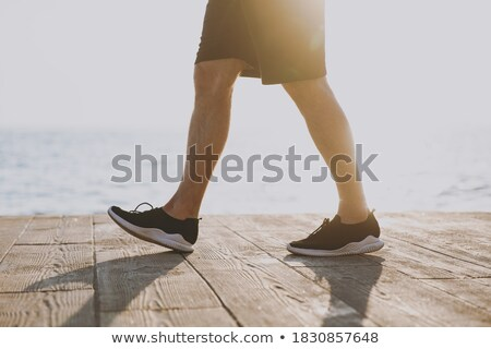 Young guy sportsman outdoors on the beach running walking. Stock photo © deandrobot