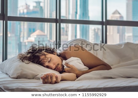 Man wakes up in the morning in an apartment in the downtown area with a view of the skyscrapers and  Stock photo © galitskaya