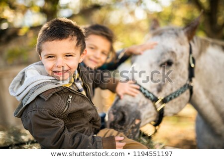 in a beautiful Autumn season of a young brother and sister with horse Stock photo © Lopolo